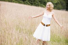 Woman standing outdoors smiling - stock photo