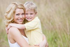 Mother holding son outdoors smiling - stock photo