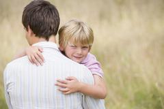 Father holding son outdoors smiling - stock photo
