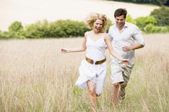 Couple running outdoors smiling Stock Photos