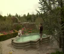 Mother and daughters enjoy fountain in Park Stock Footage