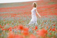 Woman walking in poppy field smiling Stock Photos