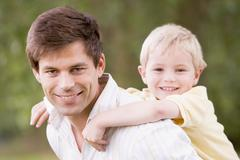 Father holding son outdoors smiling Stock Photos