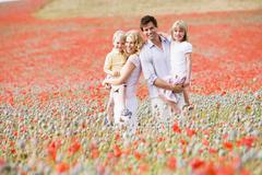 Family standing in poppy field smiling - stock photo