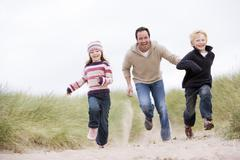 Father and two young children running at beach smiling - stock photo