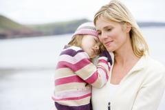 Mother holding sleeping daughter at beach - stock photo