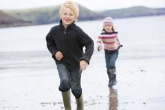 Two young children running on beach smiling Stock Photos