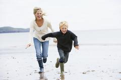Mother and son running on beach smiling - stock photo