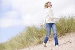 Woman walking on beach smiling - stock photo
