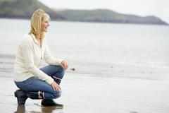 Woman crouching on beach smiling - stock photo