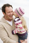 Father holding daughter kissing him at beach smiling - stock photo