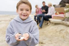 Family at beach with picnic smiling focus on boy with seashells Stock Photos