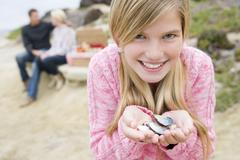 Family at beach with picnic smiling focus on girl with seashells Stock Photos