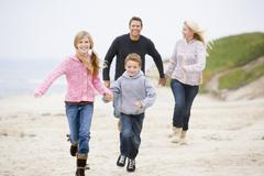Family running at beach holding hands smiling - stock photo