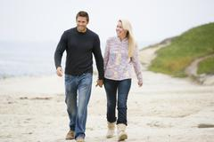 Couple walking at beach holding hands smiling - stock photo