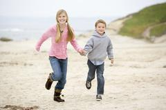 Two young children running on beach holding hands smiling Stock Photos