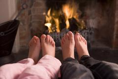 Couple's feet warming at a fireplace - stock photo
