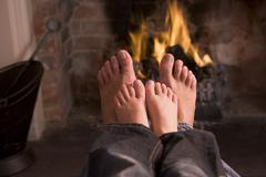 Father and son's Feet warming at a fireplace - stock photo