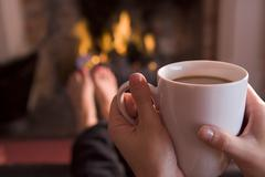 Feet warming at a fireplace with hands holding coffee Stock Photos