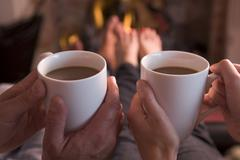 Feet warming at fireplace with hands holding coffee Stock Photos