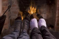 Couple's feet warming at a fireplace Stock Photos