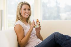 Woman in living room with coffee smiling - stock photo
