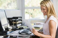 Woman in home office with computer and paperwork smiling Stock Photos
