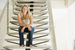 Woman sitting on stairs smiling - stock photo