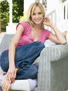 Woman sitting outdoors on patio smiling - stock photo