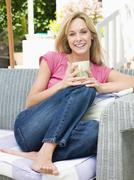 Woman sitting outdoors on patio with coffee smiling Stock Photos