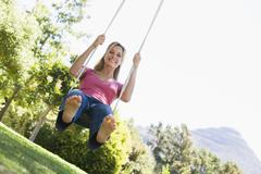 Woman on tree swing smiling - stock photo