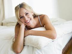 Woman lying in bedroom smiling - stock photo