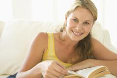 Woman in living room reading book smiling - stock photo