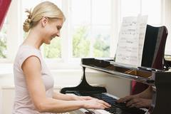 Woman playing piano and smiling Stock Photos