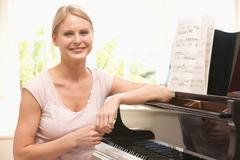 Nainen istuu pianon ja hymyilevä Kuvituskuvat