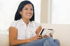 Stock Photo of Woman in living room reading book smiling