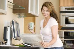 Woman in kitchen at computer with newspaper and coffee smiling Stock Photos