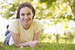 Woman lying outdoors smiling - stock photo