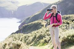 Woman on cliffside path using binoculars - stock photo
