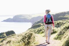 Woman walking on cliffside path - stock photo