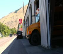 Shot of schoolbus pulling out onto street Stock Footage