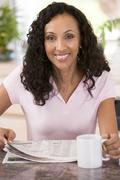 Woman in kitchen with newspaper and coffee smiling Stock Photos