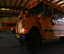 Shot of schoolbus pulling out of garage to street Stock Footage