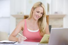 Woman in dining room with laptop smiling - stock photo