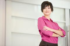 Stock Photo of Businesswoman standing indoors smiling