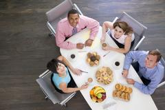 Four businesspeople at boardroom table with breakfast smiling - stock photo
