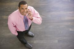 Businessman standing indoors using cellular phone smiling - stock photo