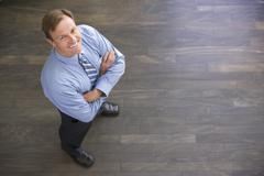 Stock Photo of Businessman standing indoors smiling