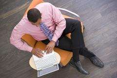 Stock Photo of Businessman sitting indoors with laptop