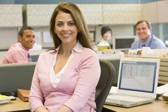 Businesswoman in cubicle smiling - stock photo